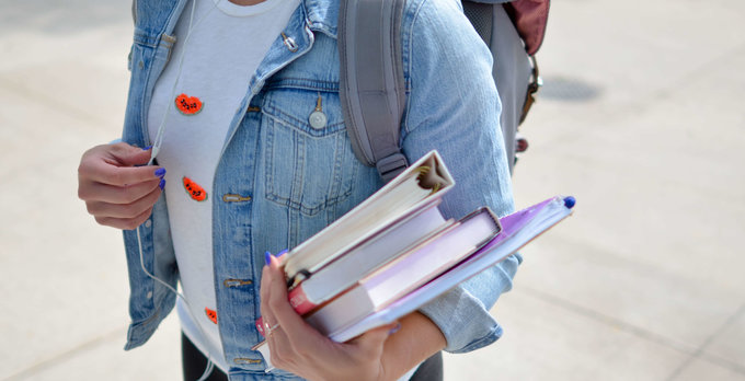 Student wearing a backpack and carrying books